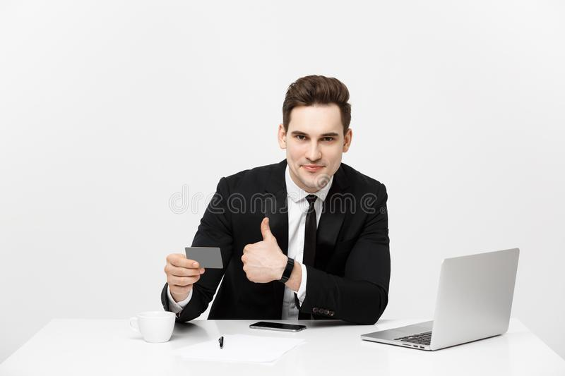 Caucasian office man in formal suit and tie demonstrating digital money in plastic credit card and showing thumb up royalty free stock images
