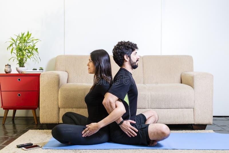Caucasian par för härlig hetero i svartkläder på blå yogam royaltyfri bild