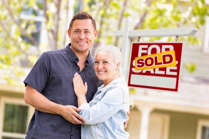 Caucasian par framme av Sold Real Estate tecknet och huset fotografering för bildbyråer