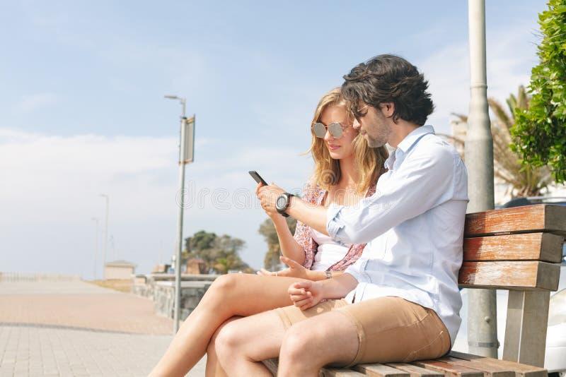 Caucasian par genom att använda mobiltelefonen, medan sitta på bänk på en solig dag royaltyfri fotografi