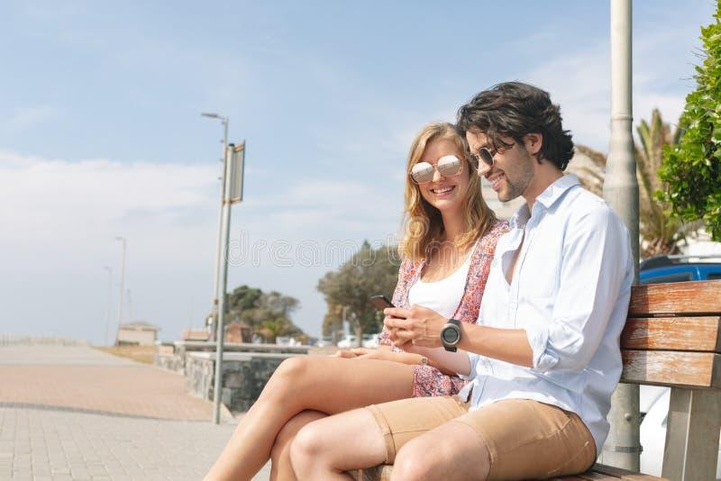 Caucasian par genom att använda mobiltelefonen, medan sitta på bänk på en solig dag royaltyfria bilder