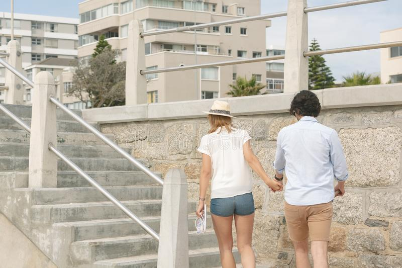 Caucasian par som går nära havssida på promenad på en solig dag royaltyfria bilder