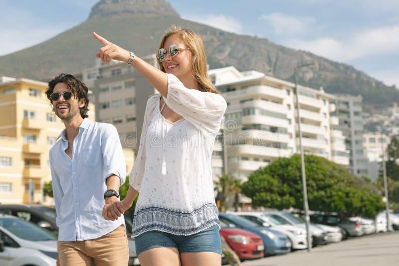 Caucasian par som går på promenaden på en solig dag royaltyfri foto