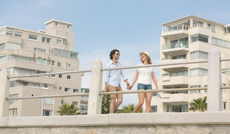 Caucasian par som går på promenaden på sjösidan fotografering för bildbyråer