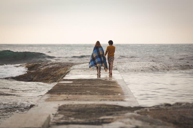 Caucasian par som går på, vaggar nära stranden royaltyfria bilder