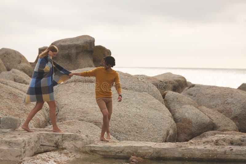 Caucasian par som går på, vaggar nära stranden arkivbilder