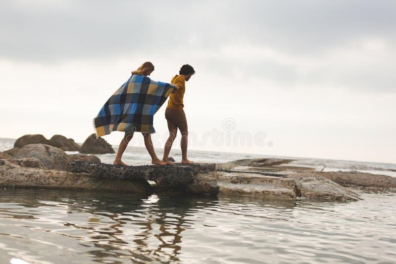 Caucasian par som går på, vaggar nära stranden arkivfoto