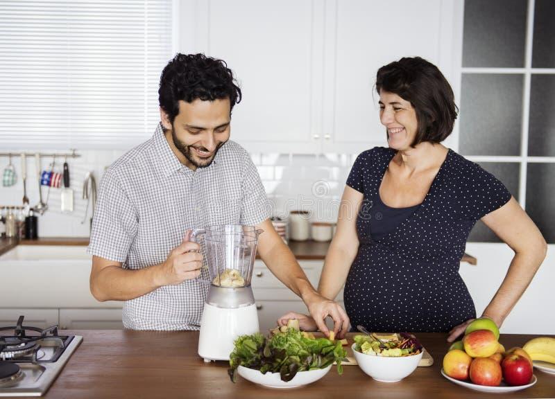Caucasian par som gör den nya smoothien royaltyfria bilder