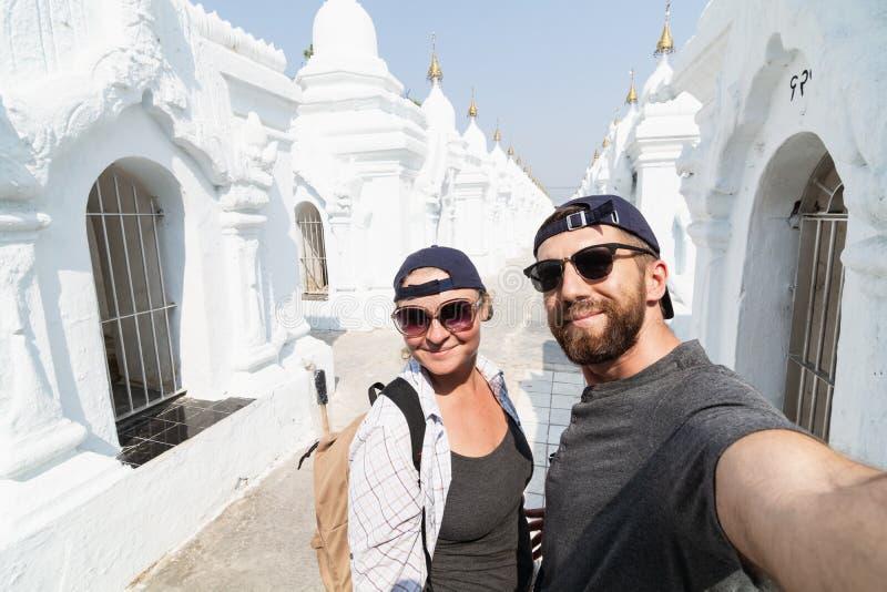 Caucasian par som gör selfie bland stupas av den Kuthodaw pagoden i Mandalay, Myanmar arkivfoto