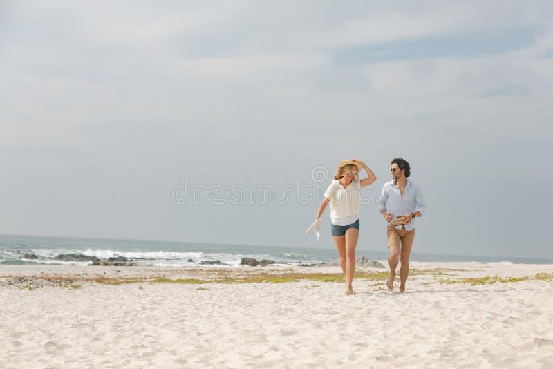 Caucasian par som kör på stranden på en solig dag royaltyfri bild