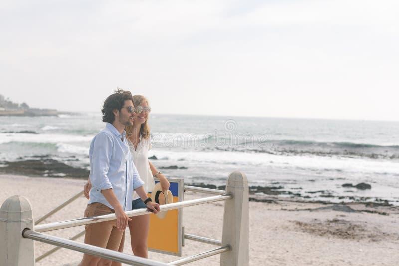 Caucasian par som kopplar av på promenaden på sjösidan arkivbild
