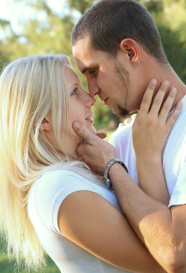 caucasian par som omfamnar parkromantiker royaltyfri fotografi