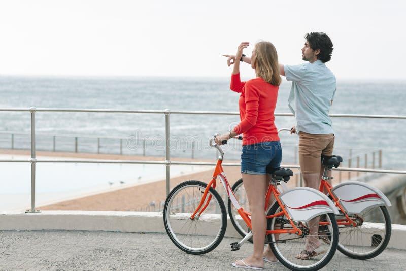 Caucasian par som påverkar varandra med de, medan rymma cykeln på promenad royaltyfri fotografi