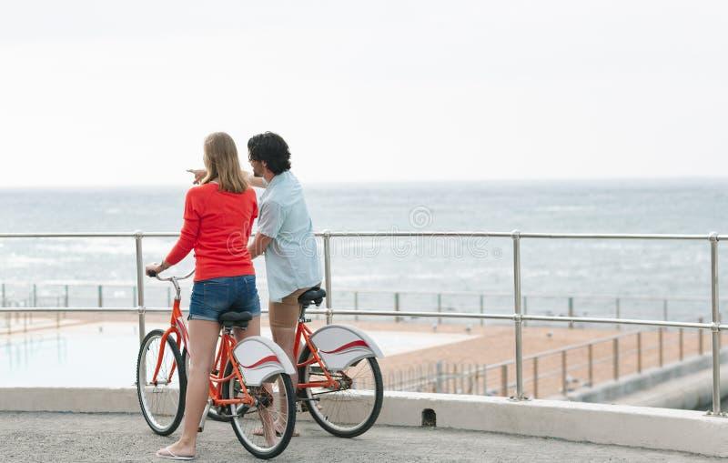 Caucasian par som påverkar varandra med de, medan rymma cykeln på promenad arkivfoto