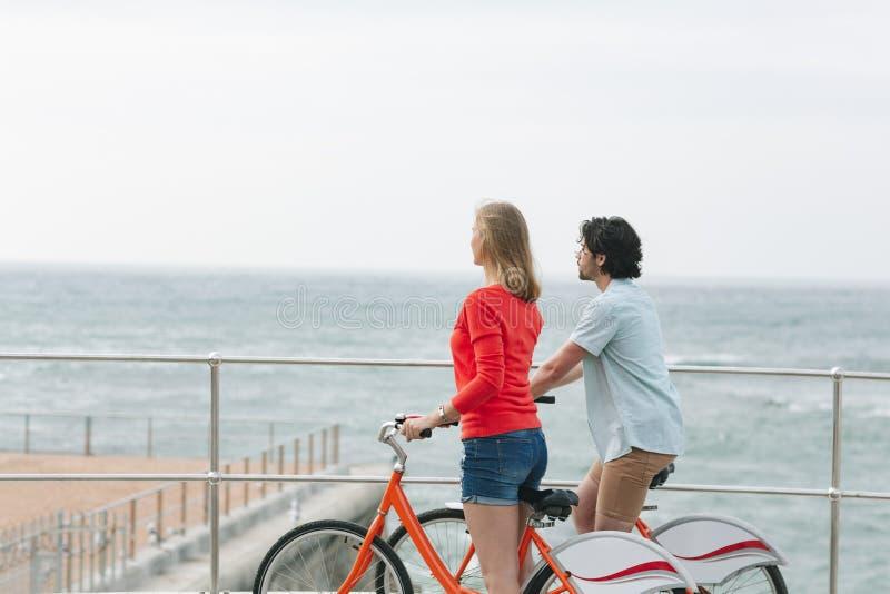 Caucasian par som påverkar varandra med de, medan rymma cykeln på promenad royaltyfria foton