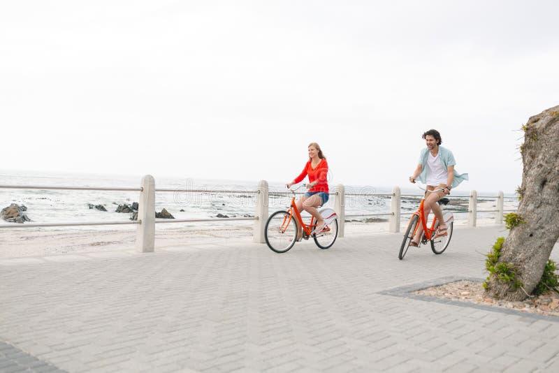 Caucasian par som rider cykeln på trottoar nära promenad royaltyfria bilder