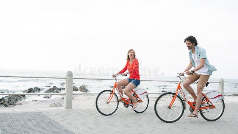 Caucasian par som rider cykeln på trottoar nära promenad arkivbilder