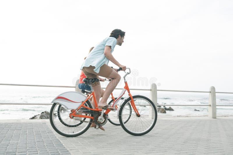 Caucasian par som rider cykeln på trottoar nära promenad på stranden royaltyfri fotografi