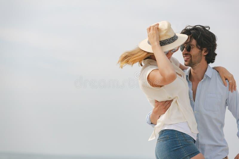 Caucasian par som ser de och dansar på stranden fotografering för bildbyråer