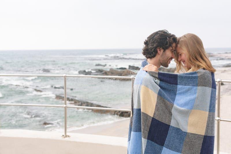 Caucasian par som slås in i filtanseende på promenad nära stranden royaltyfri fotografi