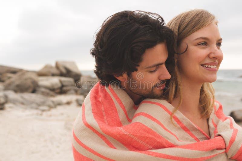 Caucasian par som slås in i filtanseende på promenad nära stranden royaltyfri foto