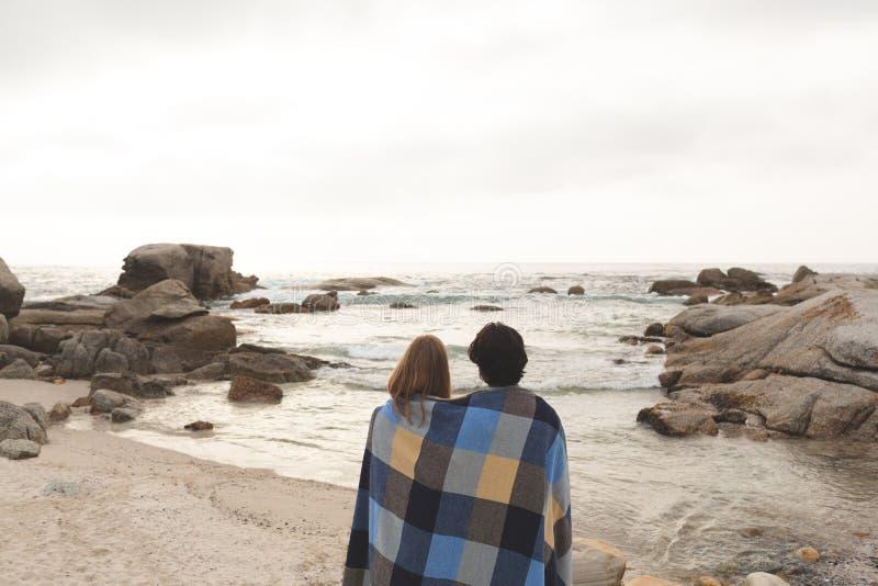 Caucasian par som slås in i filtanseende på stranden royaltyfria bilder