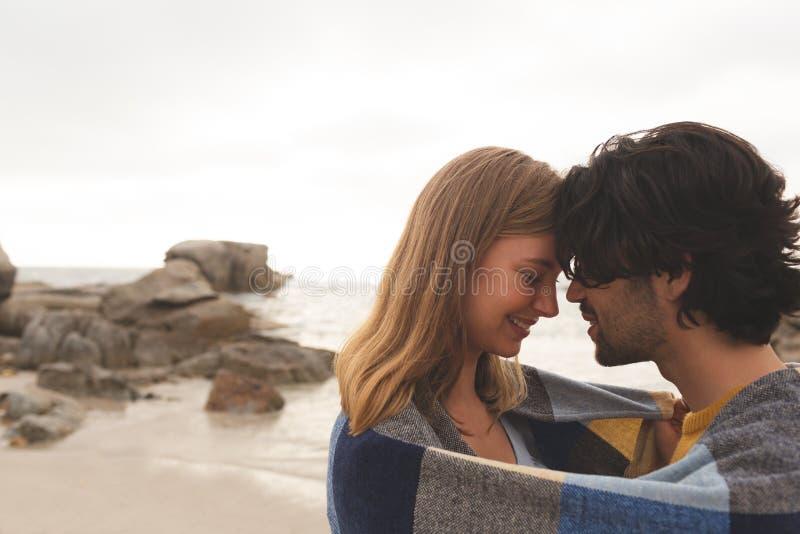 Caucasian par som slås in i filtanseende på stranden arkivbild