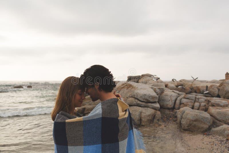 Caucasian par som slås in i filtanseende på stranden royaltyfri foto