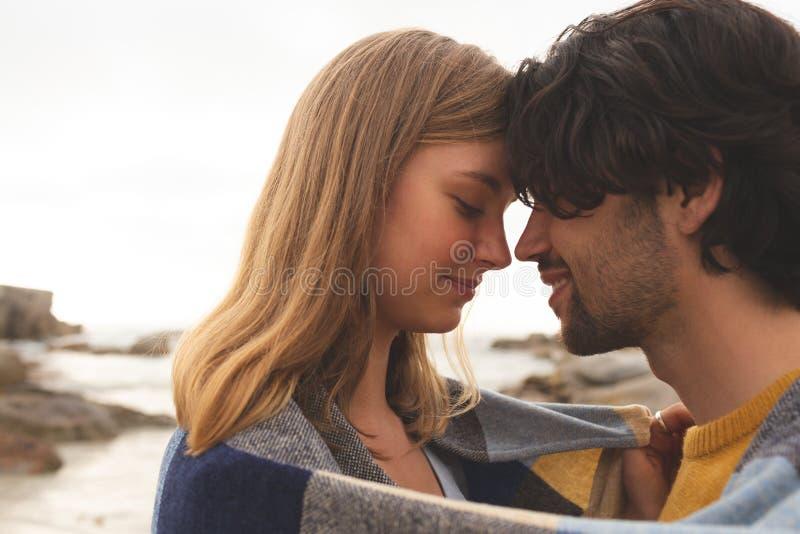 Caucasian par som slås in i filtanseende på stranden arkivbilder