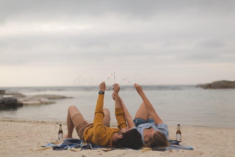 Caucasian par som spelar med brandsmällaren, medan ligga på stranden arkivfoton