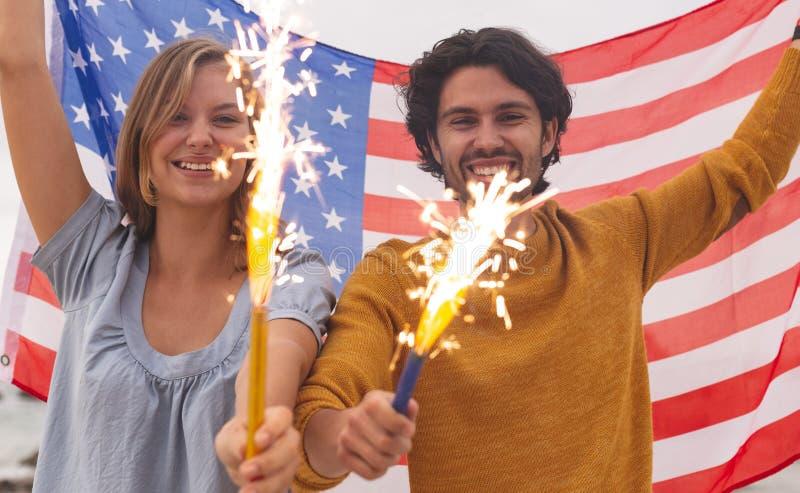 Caucasian par som spelar med brandsmällaren, medan rymma amerikanska flaggan royaltyfri fotografi