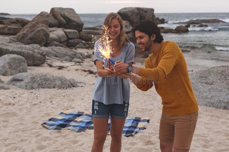 Caucasian par som spelar med brandsmällaren, medan stå på stranden royaltyfria foton