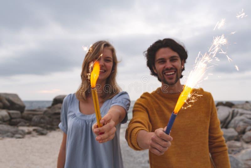 Caucasian par som spelar med brandsmällaren, medan stå på stranden arkivfoton