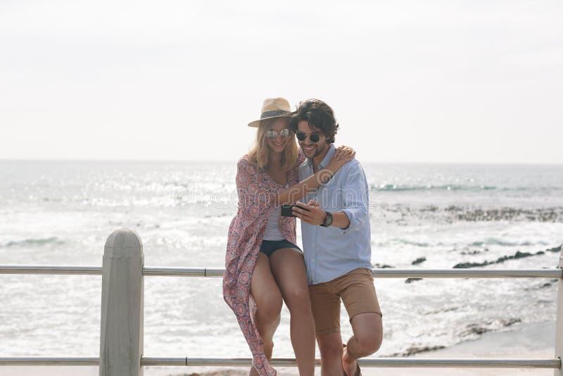 Caucasian par som tar selfie, medan sitta nära havssida på promenad på en solig dag royaltyfri foto