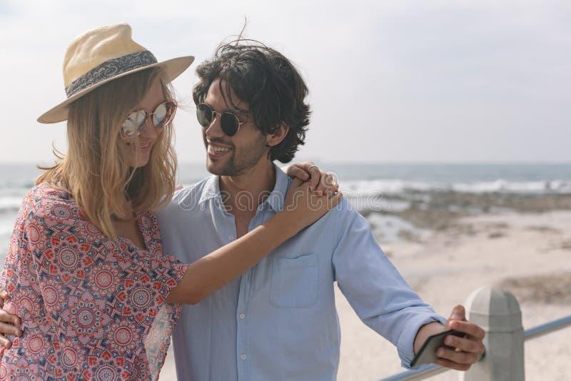 Caucasian par som tar selfie, medan sitta nära havssida på promenad arkivbild