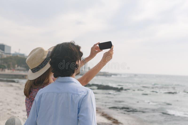 Caucasian par som tar selfie, medan stå nära havssida på en solig dag royaltyfri bild