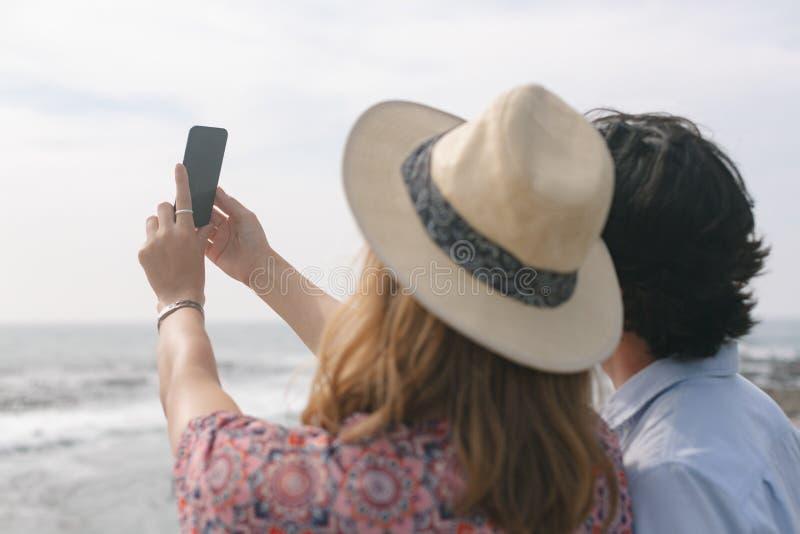 Caucasian par som tar selfie, medan stå nära havssida på promenad arkivfoto