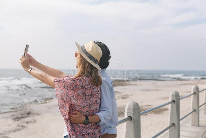 Caucasian par som tar selfie, medan stå nära havssida på promenad arkivbild