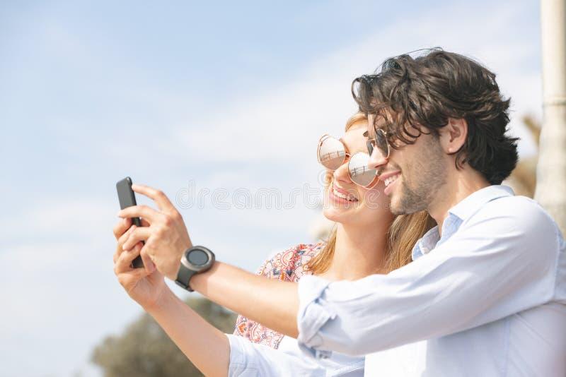 Caucasian par som tar selfie, medan stå på strandpromenad arkivbilder