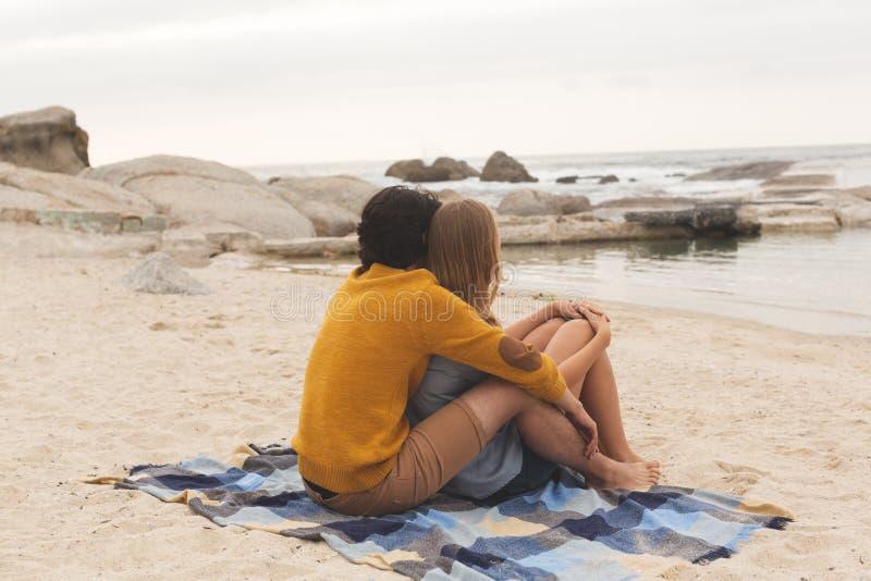 Caucasian par som tillsammans kopplar av på stranden arkivfoton