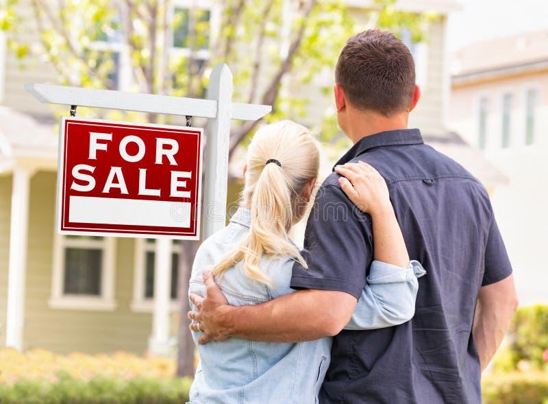Caucasian par som vänder mot framdelen av det sålda Real Estate tecknet och huset arkivbild