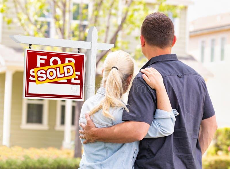 Caucasian par som vänder mot framdelen av det sålda Real Estate tecknet och huset arkivfoto
