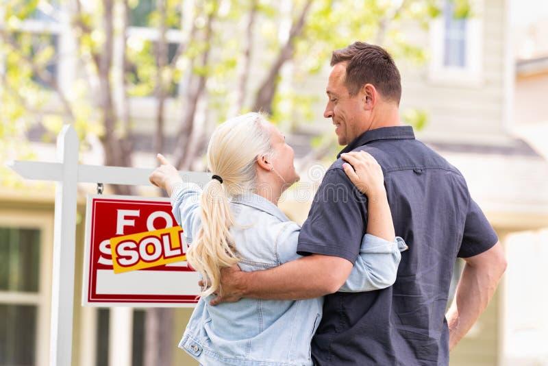 Caucasian par som vänder mot och pekar på det sålda Real Estate tecknet royaltyfria foton