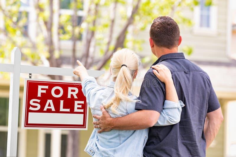 Caucasian par som vänder mot och pekar till det till salu Real Estate tecknet royaltyfri fotografi