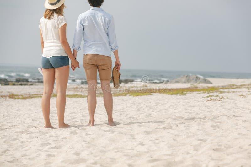 Caucasian paranseende på stranden med skodon i hand arkivbild