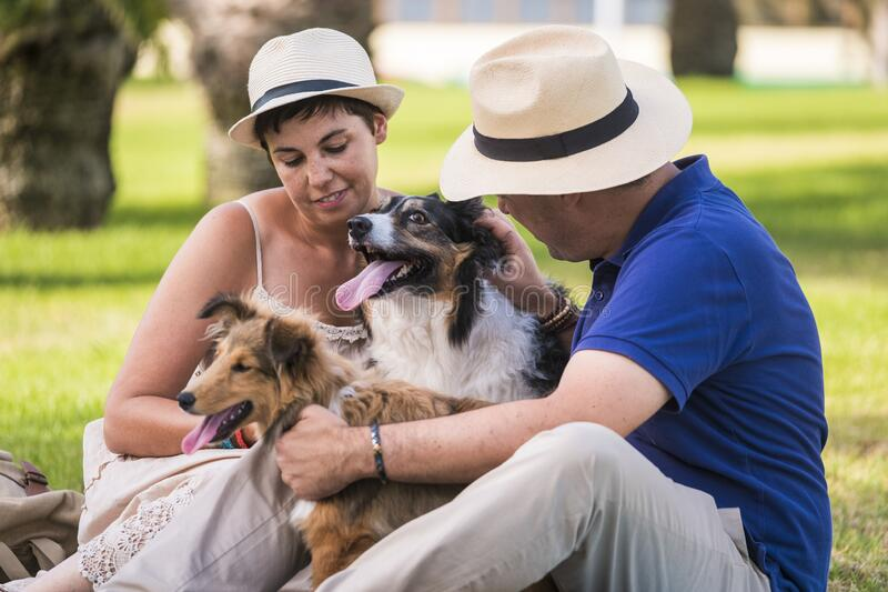 Caucasian people family concept wth dogs - happiness with domestica animals enjoying the outdoor park all together in friendship. And relationship royalty free stock photos