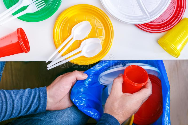 Caucasian person man throwing a plastic cup in blue garbage bag. stock images