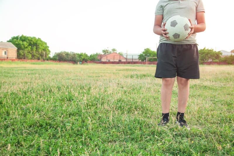 Caucasian pojke med en fotbollboll på ett fotbollfält royaltyfria foton