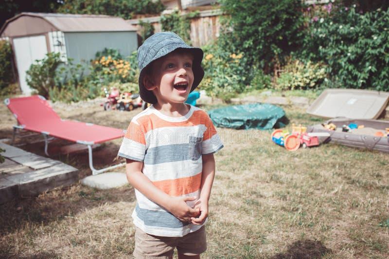 Caucasian pojke som bär den avrivna tshirten och hatten med roligt framsidauttryck utanför på husträdgård på sommardagen som gråt royaltyfria foton