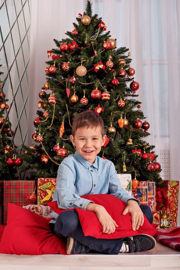Caucasian pojke som sitter nära julgranen som kramar en hemtrevlig kudde på nyårsafton royaltyfria bilder